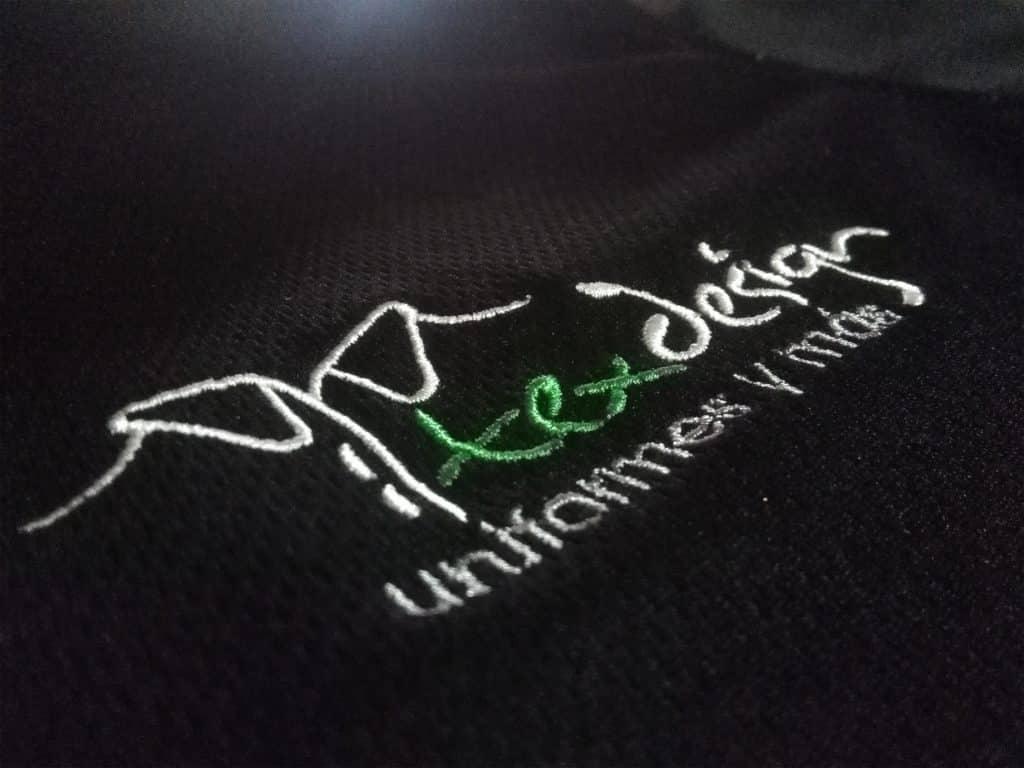 Logo de texdesign bordado sobre tela negra