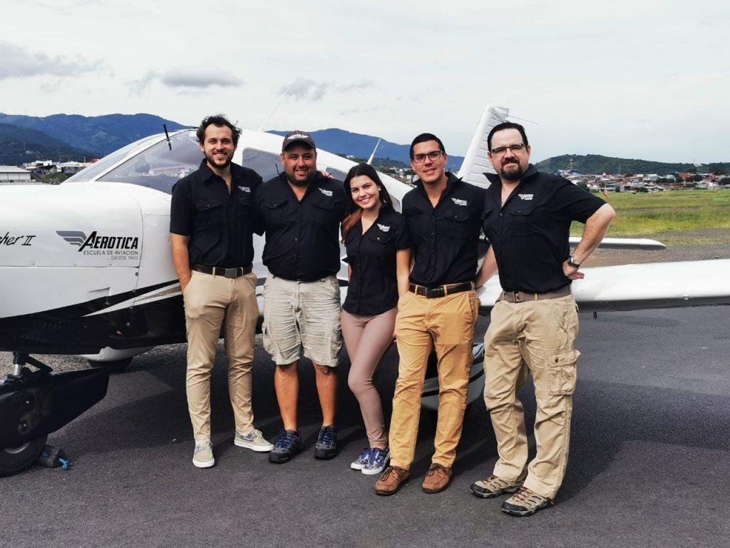 Equipo de trabajo posando frente a una avioneta en una pista de aterrizaje vistiendo camisas tipo Columbia color negro